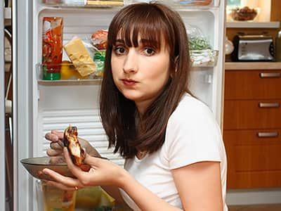 Woman Eating in Front of Refrigerator
