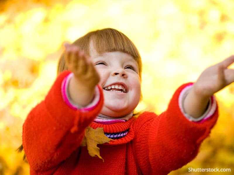 child fall throwing leaves smille laughing