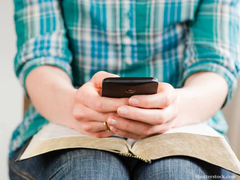 Person on smartphone over Bible