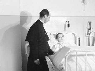 priest at a boy's hospital bed