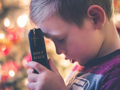 boy praying with bible