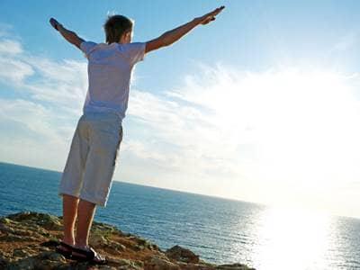 man praise by ocean