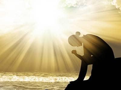 Woman praying by ocean
