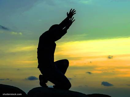 man praying arms up sunset
