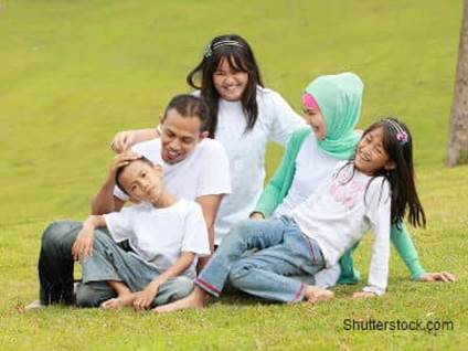 Muslim Family Playing in Grass