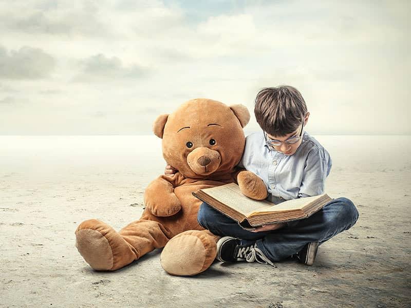 boy reading with teddy bear