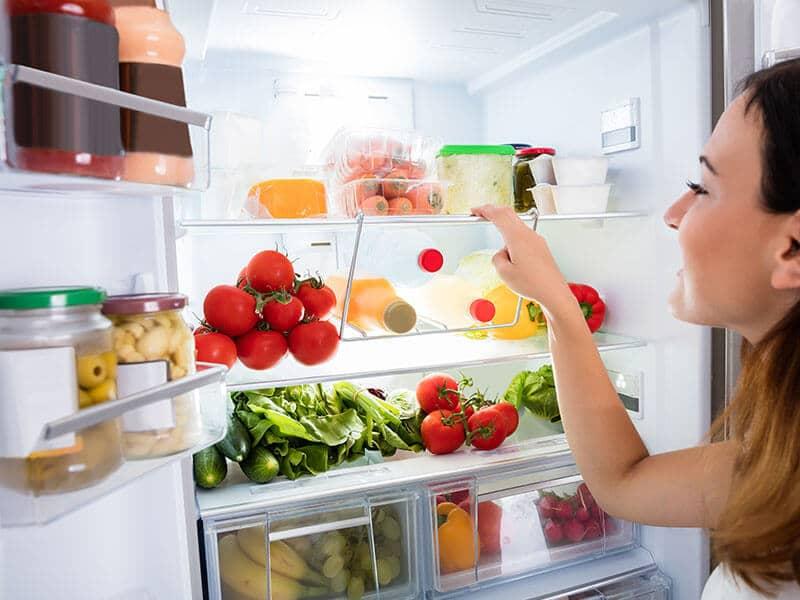woman looking in refrigerator