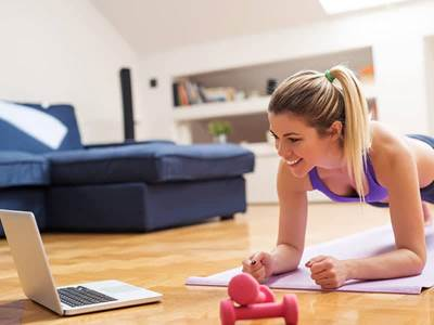 Woman on laptop with exercise weights