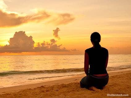 people woman praying sand beach