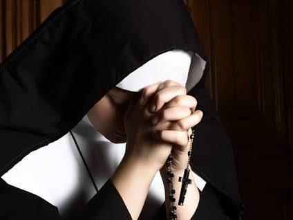 Nun praying rosary