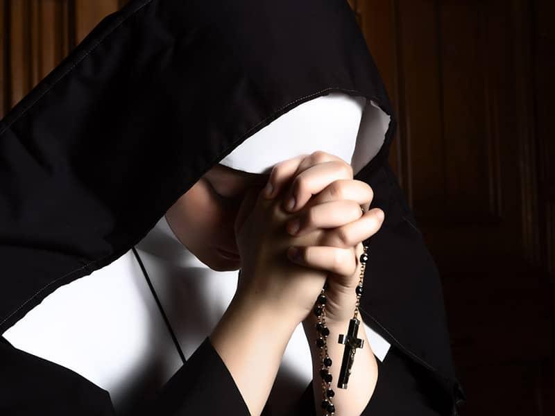 Nun praying rosary
