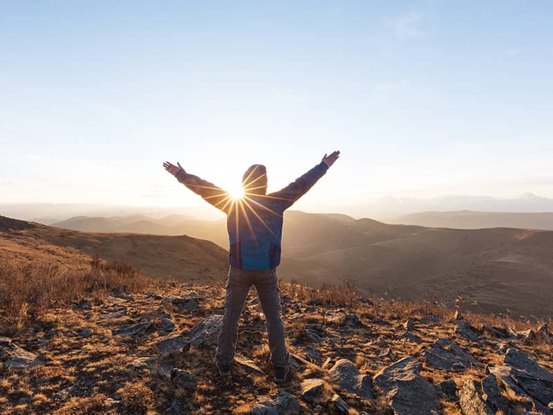 inspiration-man-arms-up-sun-mountains-morning