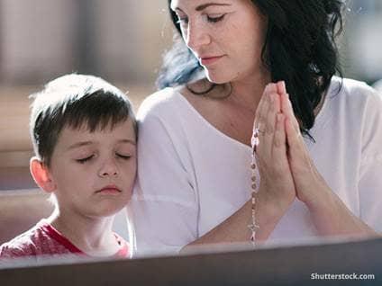 Mom and child praying in church