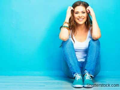 Girl Sitting by Blue Wall