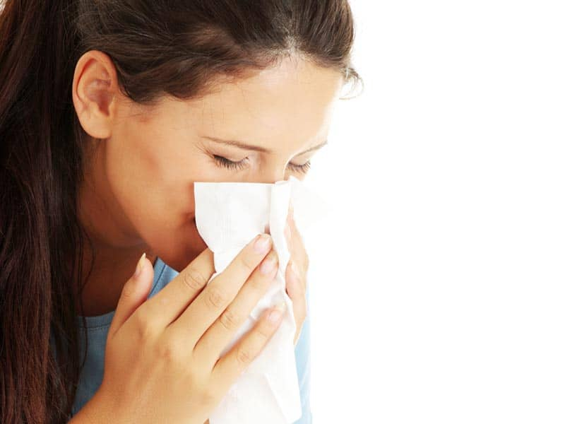 people woman blowing nose cold allergies