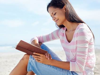 women reading book by ocean