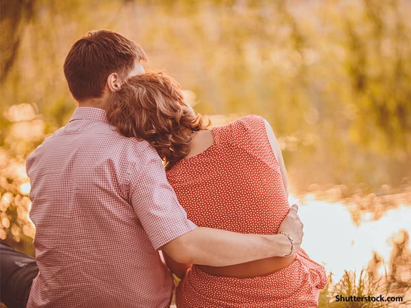 people couple hugging lake