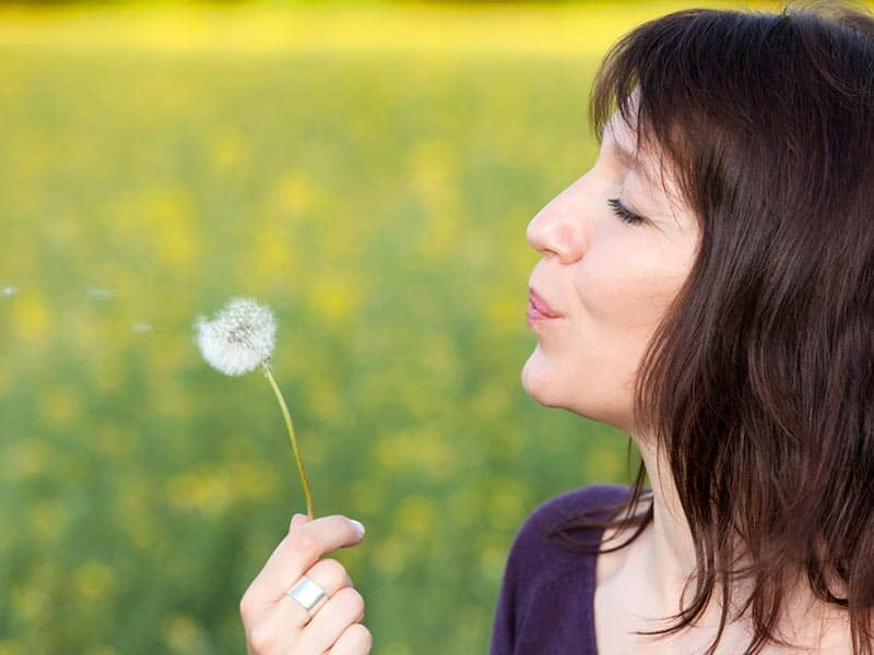 woman-blowing-dandelion-nature