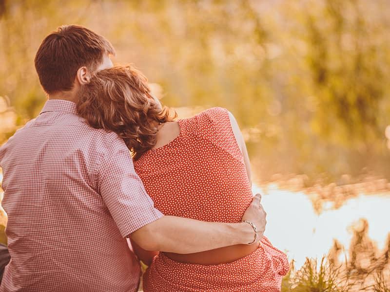 couple hugging lake