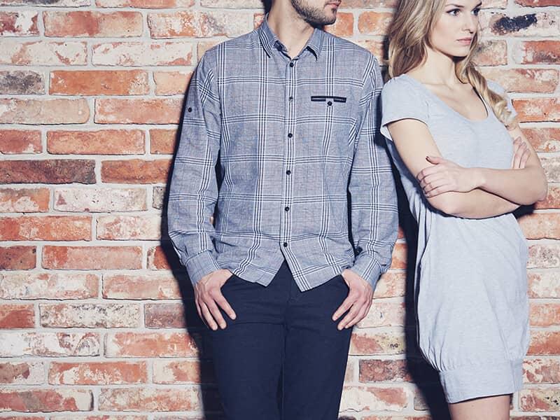 Man and woman standing at a brick wall