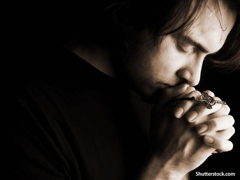 religious man praying rosary