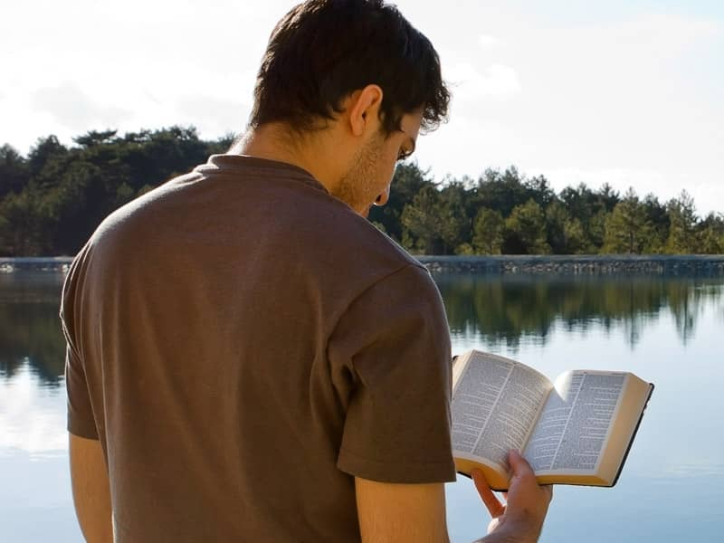 guy reading bible at lake