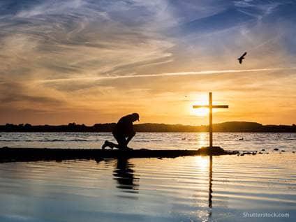 man-kneeling-prayer-cross-water