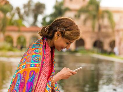 Woman in bright shawl with phone