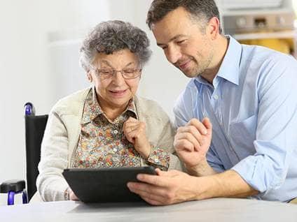 adult son teaching elderly woman computer