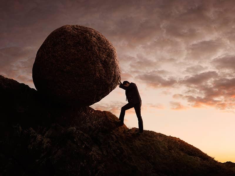 man struggling to push rock uphill
