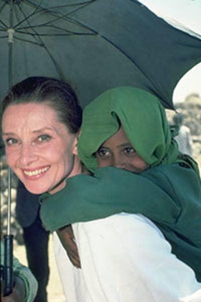 Audrey Hepburn giving kid piggy back ride