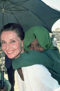 Audrey Hepburn giving kid piggy back ride