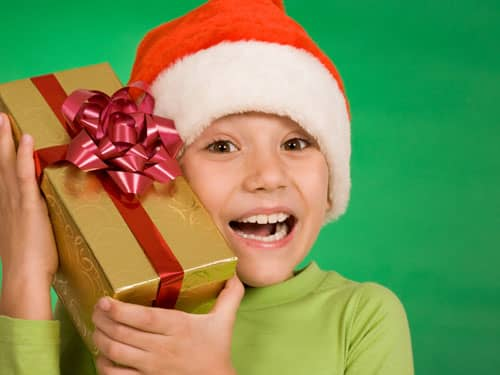 Little boy in santa hat with ear to present
