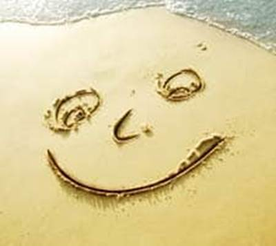 Smiley happy face drawn on beach sand