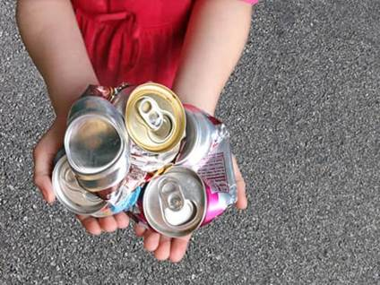 Hand holding crushed aluminum cans