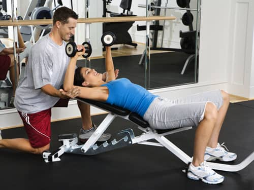 Woman lifting weights with her spotter