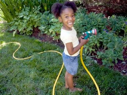 Little girl playing in garden with hose