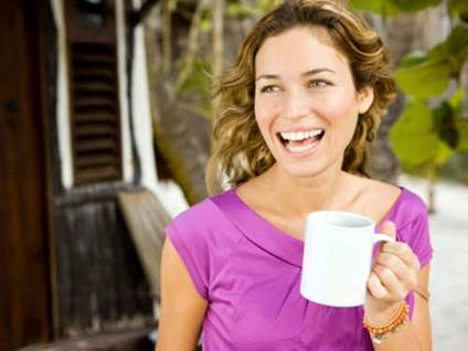 Happy woman holding mug of coffee