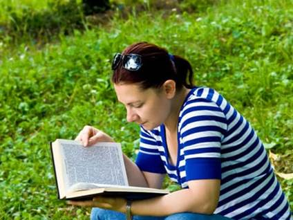 Woman reading bible in grassy field