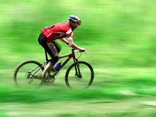 Bicycle going fast on green landscape