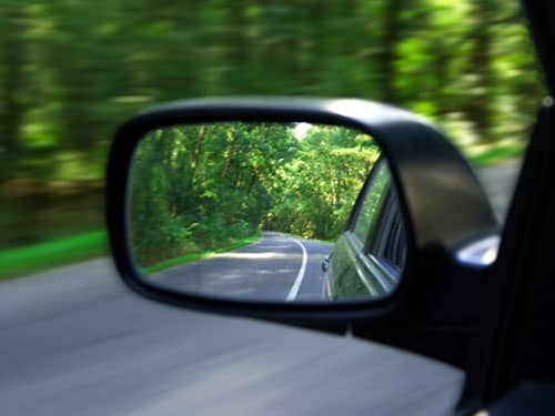 Side mirror on road in car