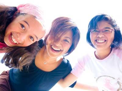 Three girls looking down into the camera, backlit.