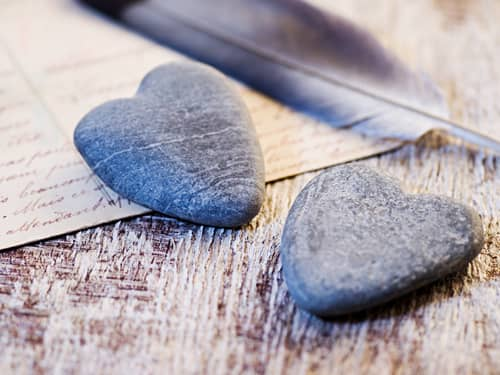 Heart-shaped stones feather letter