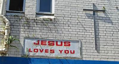 Jesus Loves You on a brick building