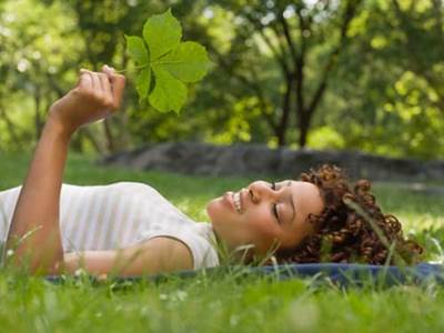 Thoughful woman holding a leaf in the summer