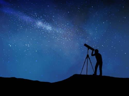 Man looking through telescope under a starry night sky