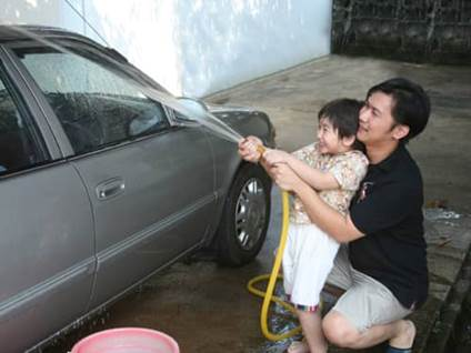 Father washing the car with his son