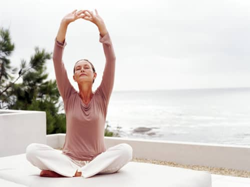 Woman sitting crossed legged in a meditative pose