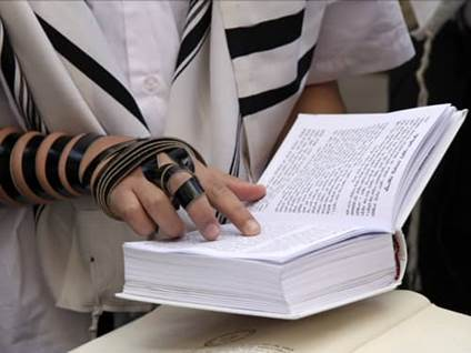 Tefillin clad hand reading from a Siddur