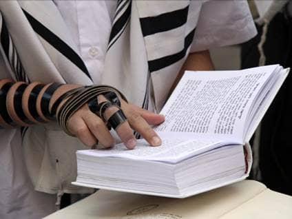 Tefillin clad hand reading from a Siddur